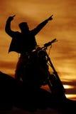 Silhouette d'un homme sur un pointage de moto Images stock