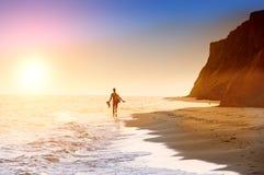 Silhouette d'un homme sur une plage abandonnée au soleil Photo stock