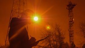 Silhouette d'un ingénieur au coucher du soleil, qui regarde les piliers de télécommunication L'ingénieur écrit des données au com banque de vidéos