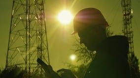 Silhouette d'un ingénieur au coucher du soleil, qui regarde les piliers de télécommunication L'ingénieur écrit des données au com clips vidéos