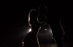 Silhouette d'un jeune couple dans l'obscurité Photographie stock libre de droits