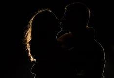 Silhouette d'un jeune couple dans l'obscurité Photos stock