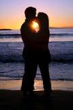 Silhouette d'un jeune couple embrassant à la plage Photos stock