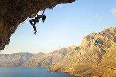 Silhouette d'un jeune grimpeur de roche féminin sur une falaise photos libres de droits