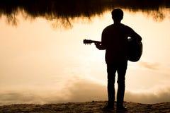 silhouette d'un jeune homme avec une guitare photographie stock
