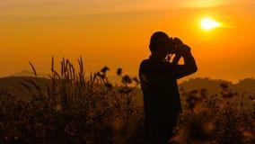 Silhouette d'un jeune qui comme à voyager et le photographe, takin Photographie stock