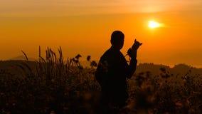 Silhouette d'un jeune qui comme à voyager et le photographe, takin Image stock