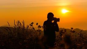 Silhouette d'un jeune qui comme à voyager et le photographe, takin Photos stock