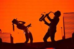 Silhouette d'un joueur de saxophone et et d'un chanteur de femme sur le s Image libre de droits