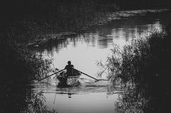Silhouette d'un pêcheur dans un bateau Photo stock