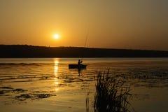 Silhouette d'un pêcheur dans un bateau avec une canne à pêche sur l'eau Photographie stock