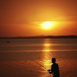 Silhouette d'un pêcheur et de sa canne à pêche pendant le coucher du soleil Image stock