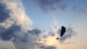 Silhouette d'un parapentiste dans le ciel de soirée planant au-dessus de la mer Image libre de droits