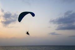 Silhouette d'un parapentiste dans le ciel de soirée planant au-dessus de la mer Photos stock