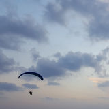 Silhouette d'un parapentiste dans le ciel de soirée planant au-dessus de la mer Photo stock