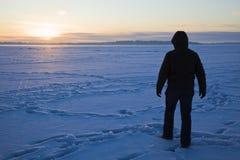 Silhouette d'un pêcheur marchant sur le lac Photographie stock