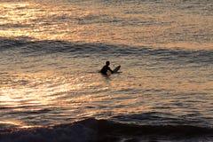 Silhouette d'un surfer seul attendant une vague près de la plage au coucher du soleil Photos stock