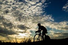 Silhouette d'un triathlete dans le coucher du soleil Images libres de droits