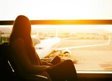 Silhouette d'un voyageur de jeune femme attendant à l'aéroport le départ Photos stock