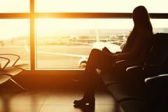 Silhouette d'un voyageur de jeune femme attendant à l'aéroport le départ Photo stock