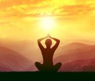 Silhouette d'un yoga de pratique de femme dans les montagnes Photographie stock