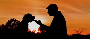 Silhouette d'une amitié profonde entre l'homme et le chien Photos stock
