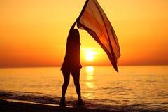 Silhouette d'une danse de dame avec un drapeau Image libre de droits