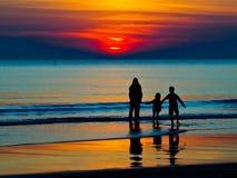 Silhouette d'une famille dans le coucher du soleil Images libres de droits