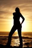 Silhouette d'une femme au coucher du soleil Photographie stock
