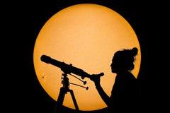 Silhouette d'une femme avec l'observation sûre de Sun de télescope photographie stock libre de droits