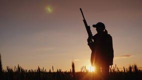 Silhouette d'une femme avec un revolver en ses mains Chasseur dans le domaine au coucher du soleil Photographie stock libre de droits