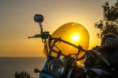 Silhouette d'une femme de cycliste se reposant sur la plage sur le fond de coucher du soleil, appréciant la liberté et le mode de photographie stock libre de droits