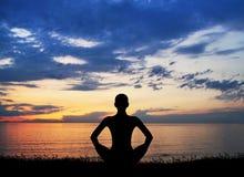 Silhouette d'une femme faisant le yoga sur un coucher du soleil Photos libres de droits