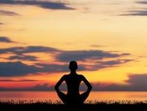 Silhouette d'une femme méditant sur le rouge Photographie stock libre de droits