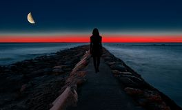 Silhouette d'une femme marchant par la mer Images libres de droits