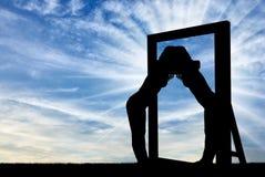 Silhouette d'une femme narcissique étreignant sa réflexion dans un miroir Photographie stock
