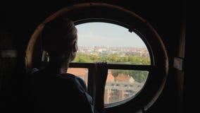 Silhouette d'une femme regardant dans une fenêtre ronde sur les dessus de toit de la ville de Copenhague au Danemark banque de vidéos