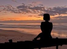 Silhouette d'une femme s'asseyant dans un lever de soleil Photos libres de droits