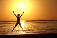 Silhouette d'une femme sautante dans la perspective du soleil se levant au-dessus de la mer image libre de droits