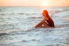 Silhouette d'une fille dans l'eau au coucher du soleil photo stock
