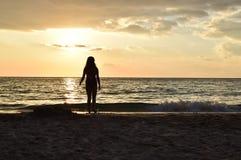 Silhouette d'une fille dans la lumière de coucher du soleil à la plage photo libre de droits