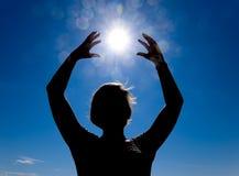 Silhouette d'une fille dans la perspective du soleil et du ciel bleu Des mains sont augmentées jusqu'au soleil Images libres de droits
