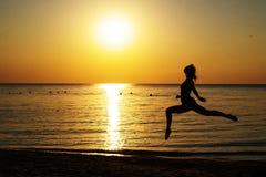 Silhouette d'une fille dans un maillot de bain fonctionnant le long de la plage sur le fond de l'aube image libre de droits