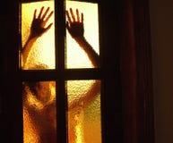 Silhouette d'une fille derrière une porte en verre Photographie stock
