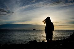 Silhouette d'une fille seul se tenant sur le bord de la mer avec le beau ciel sur le fond photos libres de droits