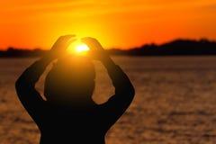 Silhouette d'une fille sur le fond du soleil de soirée, coucher du soleil rouge Photographie stock