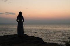 Silhouette d'une fille sur un lever de soleil de fond de coucher du soleil sur la mer photos stock