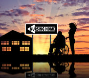 Silhouette d'une infirmière s'occupant d'un homme plus âgé dans un fauteuil roulant Image stock