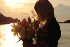 Silhouette d'une jeune femme avec des lis Image stock