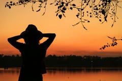 Silhouette d'une jeune femme détendant contre le beau ciel vif de coucher du soleil de couleur par le bord de mer images stock